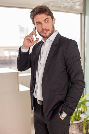 seriousness: Handsome businessman is standing and talking on the mobile phone. He is looking aside with seriousness and confidence