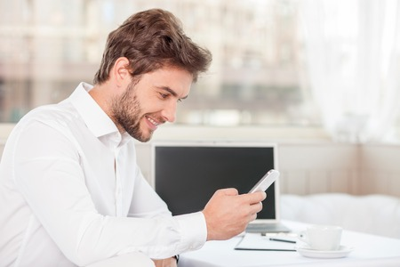 Successful businessman is using his mobile phone. He is looking at it and smiling. The guy is sitting at the table near notebook and a cup of coffee. Copy space in right side Stock Photo
