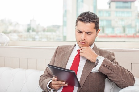 seriousness: Cheerful businessman is sitting and holding a laptop in his hand. He is looking at it with seriousness and touching his chin pensively. Copy space in left side Stock Photo
