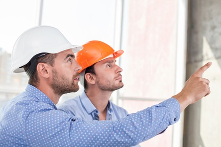 building work: Attractive architect is explaining to a foreman the main concepts of construction. He is pointing his finger forward. They are looking at this place with attention and seriousness Stock Photo