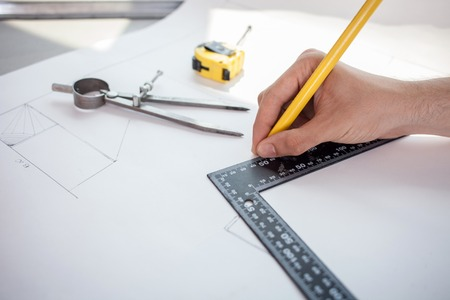 blueprint: Close up of hand of engineer blueprinting the plan of new building with a ruler and pencil. There are a compass and tape-measure on the table