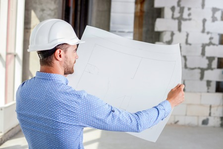 ownership and control: Handsome architect is analyzing the sketches of building. He is looking at it with aspirations. The man is raising the blueprint with proud