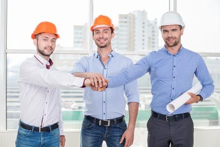 positivismo: Arquitecto joven y atractiva y dos constructores se están uniendo sus manos. Están sonriendo amigable. Los hombres confían entre sí. Ellos son el verdadero equipo
