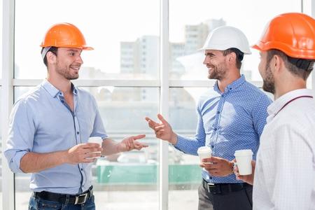 Aantrekkelijke bouwers zijn koffie drinken op een break. Ze praten en lachen. De mannen zijn op zoek naar elkaar met vertrouwen