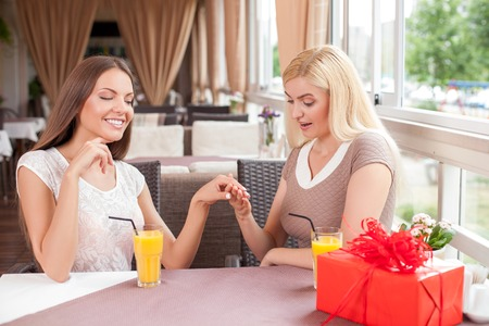 boasting: Pretty girls are sitting at the table and drinking juice. The brunette girl is showing the ring to her friend and smiling boastfully. The blond lady is looking at the gift with admiration