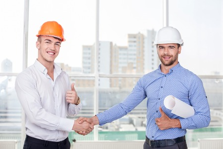 concerning: Attractive foreman and cheerful architect are shaking hands happily. They made a deal concerning the plan of a new project. They are giving thumbs up and smiling