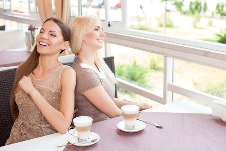 secretly: Cheerful women are resting together in cafe. They are sitting at the table and leaning on each others back. One girl is tickling another woman secretly. They are smiling Stock Photo
