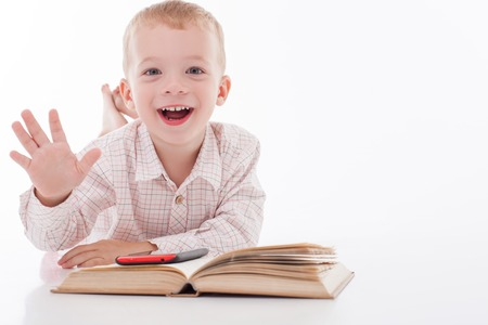 he is a traditional: Pretty boy is using a mobile phone for reading. He prefers modern technologies to traditional books. The boy is smiling and raising his arm up. Isolated and copy space in right side