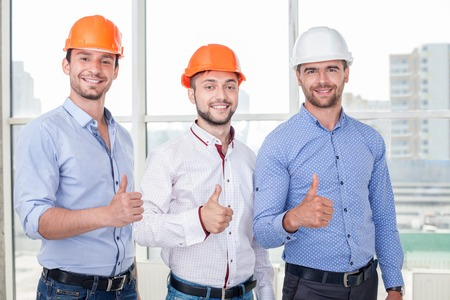 Cheerful architect and workers are giving thumbs up with joy. They have already done the work of project. The men are smiling and looking at the camera with happiness 版權商用圖片
