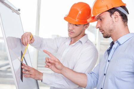 arquitecto: Arquitectos atractivos est�n trabajando en un proyecto. Un constructor est� dibujando bocetos en modelo con la inspiraci�n. Otro hombre est� se�alando con el dedo a �l y dar consejos relativos a un plan serio