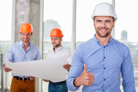 Attractive architect is giving thumb up. The man is smiling and looking at the camera with happiness. His plan was approved. Two builders are looking at sketches of building on background