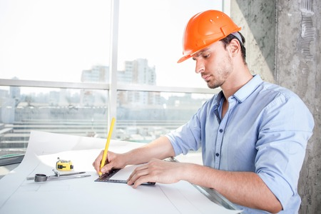 concentration: Attractive architect is drawing the sketches of new building with concentration. He is sitting at the table and holding a ruler and pencil. He is serious and confident