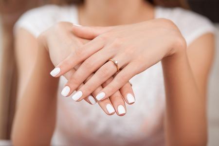 manicura: Cerca de las manos de la mujer que muestra el anillo con el diamante. Ella está comprometida Foto de archivo