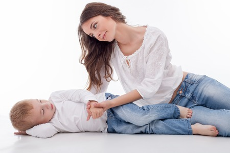 gentleness: Pretty woman is lying near her son. They are holding hands and looking at each other with gentleness. Isolated on background Stock Photo