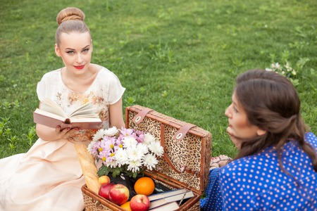 poem: Beautiful women are resting and sitting on grass near the basket of food. The blond girl is reading a poem aloud and smiling with pleasure. Her friend is listening to her attentively