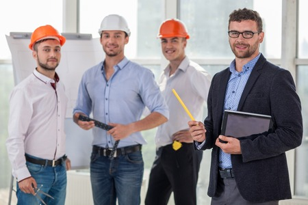 Handsome young builders and architect are working on a new project. They are discussing the plan of building and drawing sketches. The architect is holding a laptop. They are smiling