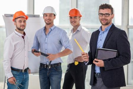 Knappe jonge bouwers en architect werken aan een nieuw project. Zij bespreken het plan van de bouw en tekenen schetsen. De architect houdt een laptop. Ze zijn lachend Stockfoto