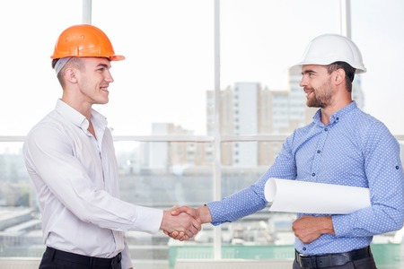 Cheerful architect and attractive foreman are shaking hands. The new plan was approved. They are smiling and looking at each other happily
