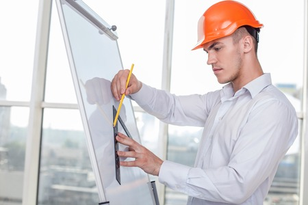 architect tools: Cheerful architect is drawing sketches of building with a ruler and pencil. He is doing it on a vertical board with inspirations Stock Photo