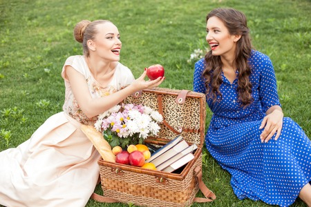 girl apple: Beautiful girls are making picnic in the nature. They are sitting on grass near a basket of food. The girl is proposing an apple to her friend. They are laughing