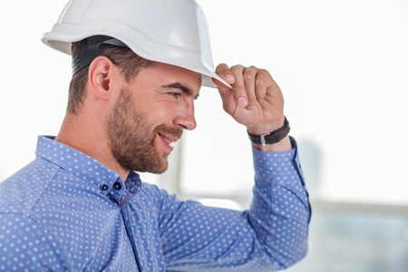 side job: Handsome architect is adjusting a white helmet on his head. He is looking forward and smiling with happiness. The man likes his job. Copy space in right side Stock Photo
