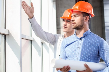 seriousness: Cheerful young foreman is showing to the architect the problems of construction. He is pointing his arm sideways. The men are looking aside with seriousness
