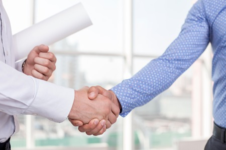 building trust: Close up of arms of architect and foreman shaking hands. The new plan was approved. They built a consensus. The architect is holding a blueprint