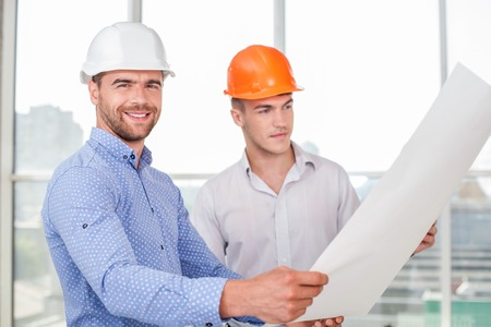 arquitecto: Handsome architect is showing the layout of building to a foreman. The worker is looking at it with concentration. The architect is looking at the camera and smiling with joy