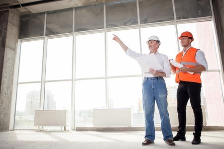architecte principal et jeune constructeur discutent nouveau projet. L'architecte pointe son doigt sur le côté sérieux. Le contremaître, il cherche avec intérêt et souriant. espace de copie dans le côté gauche