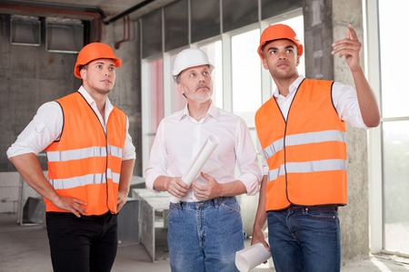 seriousness: Cheerful young foreman is sharing his ideas with builders. He is pointing his finger sideways with seriousness. The old architect and a worker are looking there with interest