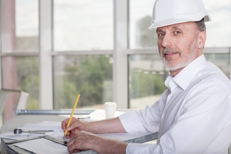 architect drawing: Cheerful old architect is sitting at the table and drawing sketches of building. He is looking at the camera and smiling