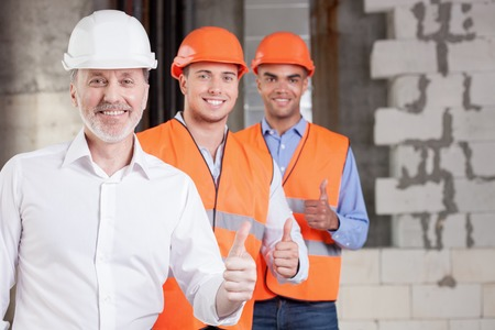 contractor: Skilled old architect and young workers are giving thumbs up. Their project was approved. The men are smiling and looking at the camera with happiness. Copy space in right side