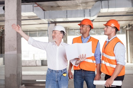 Senior architect is expressing his ideas concerning building. He is pointing his arm sideways and smiling. The man is holding a blueprint. The builders are looking aside with interest and joy