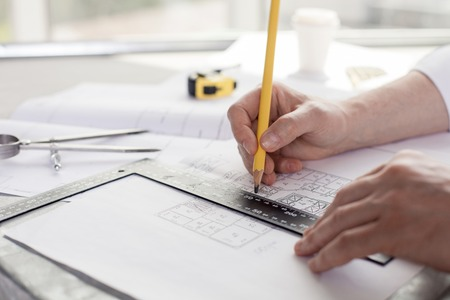 architect office: Close up of hands of architect drawing sketches of construction. He is holding a pencil and a ruler