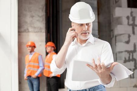 Ervaren oude architect is te kijken naar het plan van de bouw met verbazing. Hij raakt zijn gezicht met shock. De arbeiders staan in de buurt van hem met rust Stockfoto