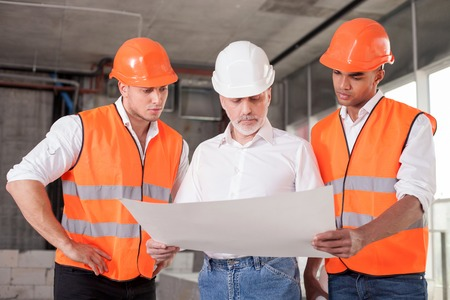 Successful old architect and two workers are discussing the plan of building. They are looking at the blueprint with seriousness