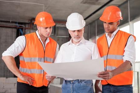 arquitecto: Exitosa arquitecto de edad y dos trabajadores est�n discutiendo el plan de la construcci�n. Ellos est�n buscando en el plan con seriedad