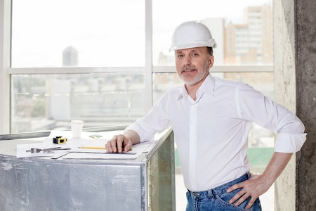he old: Skilled old architect is drawing sketches of building. He is leaning on a surface where a blueprint is situated. The man is looking forward and smiling
