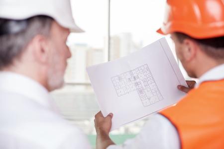 arquitecto: Experimentado viejo arquitecto y capataz joven est�n trabajando en el plan de la construcci�n. El trabajador est� llevando a cabo un proyecto. Los hombres est�n mirando bocetos de concentraci�n. Centrarse en un documento