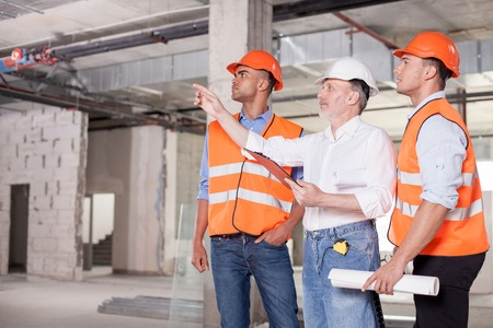 project planning: Experienced old architect is explaining to construction team the concepts of project. He is pointing his finger sideways seriously. The workers are looking there with interest. Copy space in left side
