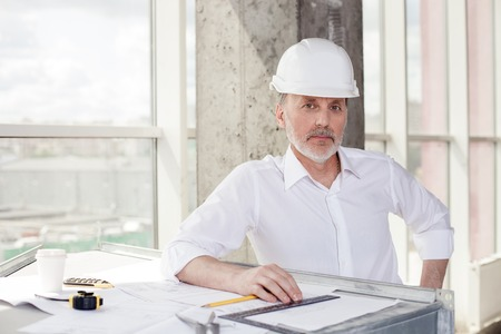 seriousness: Experienced senior engineer is making plan of building. He is standing near a blueprint and other equipment. The man is looking at the camera with seriousness