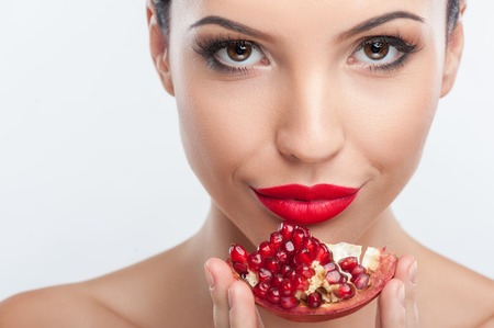 a pomegranate: Close up of female face. The beautiful girl is touching a pomegranate to her chin. Her lips are red. She is smiling and looking at the camera with joy. Isolated Stock Photo