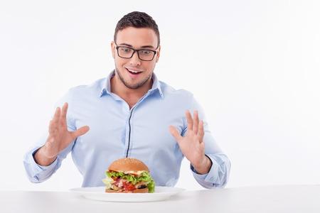 Gars intéressant est à la recherche à l'hamburger avec la tentation. Il est prêt à manger. Le gars est assis à la table et heureusement souriant. Isolé sur fond et copier espace côté droit