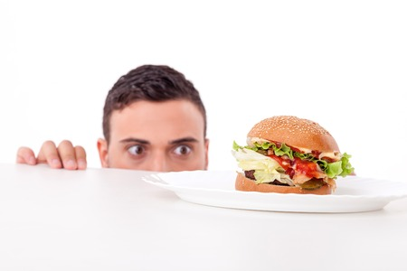 adult sandwich: Cheerful guy is hiding behind a table and peeping through it. He is looking at an unhealthy hamburger with desire. Isolated on background