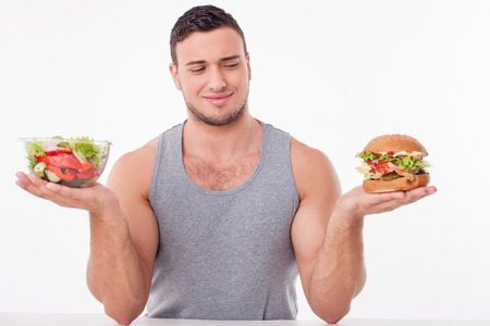 hamburger: Cheerful man is holding a bowl of salad and a hamburger in his hands. The man is looking at unhealthy food with disgust. The boy is sitting at the table. Isolated on background Stock Photo