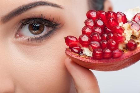 witaminy: Bliska kobiecych oczu. Kobieta dotyka kawałek granatu do twarzy z przyjemności