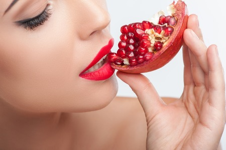Close up of beautiful girl eating a pomegranate with pleasure. She closed her eyes with enjoyment