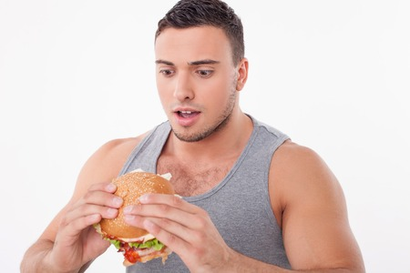 adult sandwich: Attractive guy is holding a sandwich in his hands. He is looking at this unhealthy food with shock. Isolated on background Stock Photo