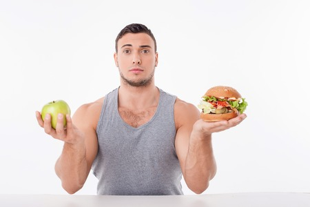 Attractive fit guy is lost in choice between healthy and unhealthy eating. He is holding an apple and hamburger in both his hands. The guy is puzzled. Isolated on background