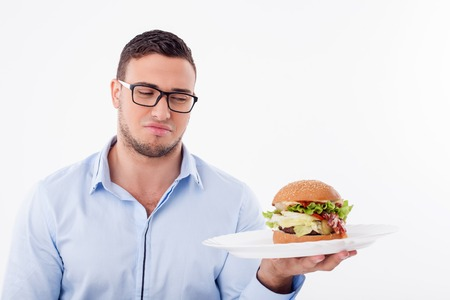 disgust: Handsome guy is holding the plate with hamburger. He is looking at it with disgust. Isolated on background